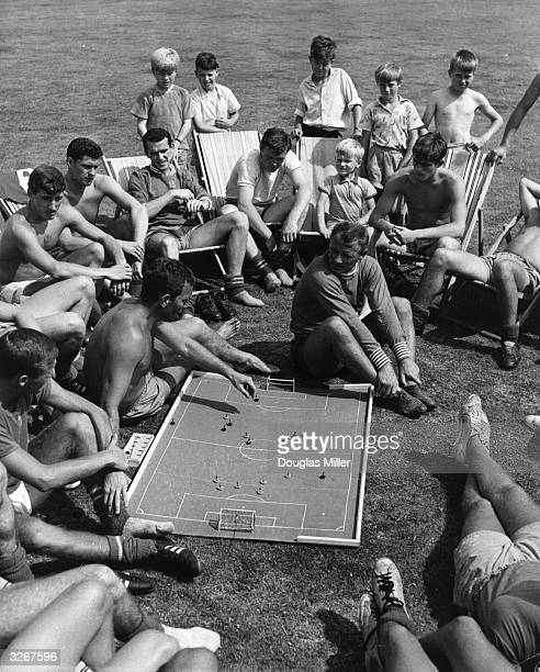 Chelsea coach Dave Sexton using a miniature football game to demonstrate tactics during a talk with his players and manager Tommy Doherty