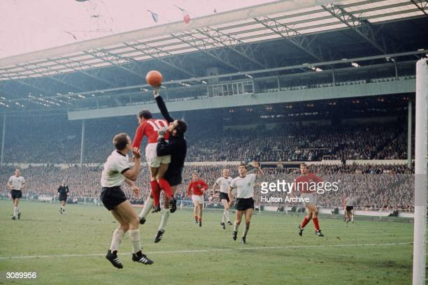 England player Geoff Hurst competes with the West German goalkeeper Hans Tilkowski for an aerial ball during the World Cup Final at Wembley Stadium