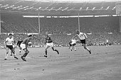 English footballer Jackie Charlton watching his teammate George Cohen block a shot by the German forward Siegfried Held during the World Cup final at...