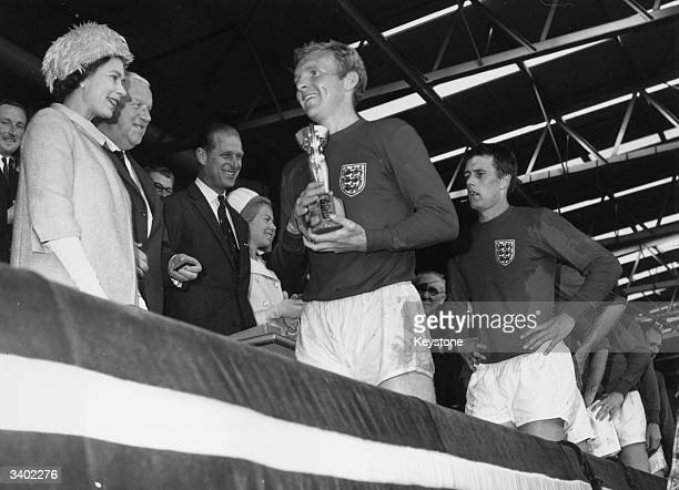 Queen Elizabeth II smiles after presenting England captain Bobby Moore with the Jules Rimet trophy following England's 42 victory over West Germany...
