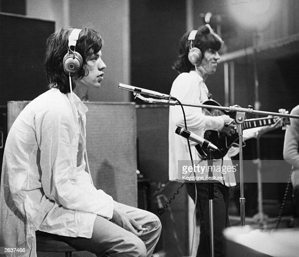 Rolling Stones singer Mick Jagger foreground and guitarist Keith Richards at work in a recording studio during the filming of director Jean Luc...