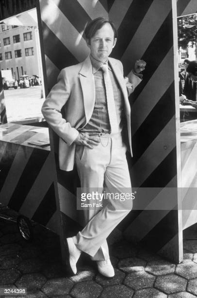 Portrait of American author Tom Wolfe leaning against a kiosk New York City