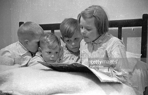 Connie Whitham reading a bed time story to her younger brothers in bed Original Publication Picture Post 2017 Bringing Up A Very Big Family pub 1945