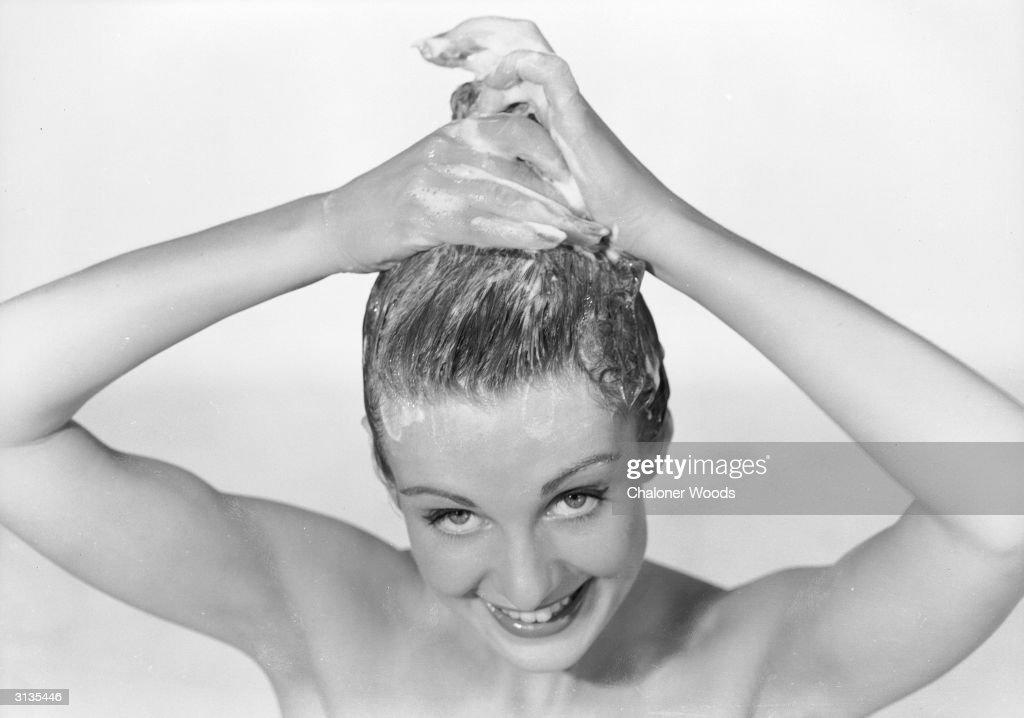 A woman applies shampoo to her hair