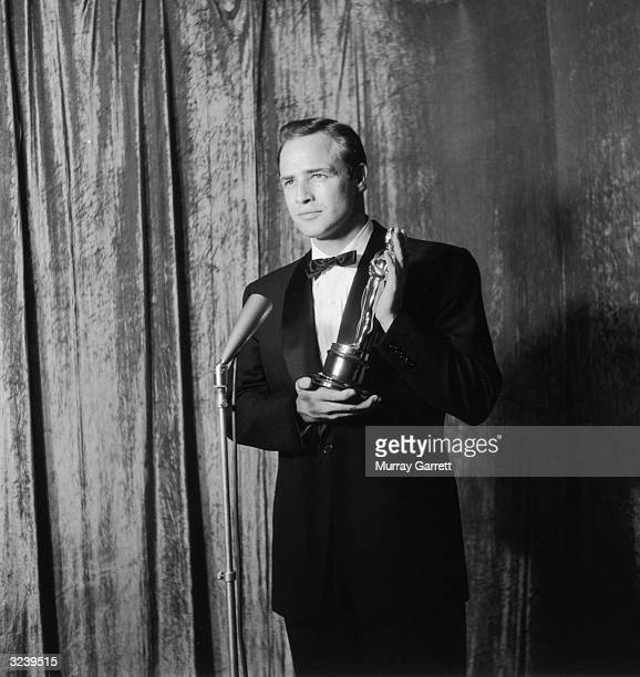 EXCLUSIVE American actor Marlon Brando holds his Best Actor Oscar statue while standing behind a microphone backstage at the Academy Awards RKO...