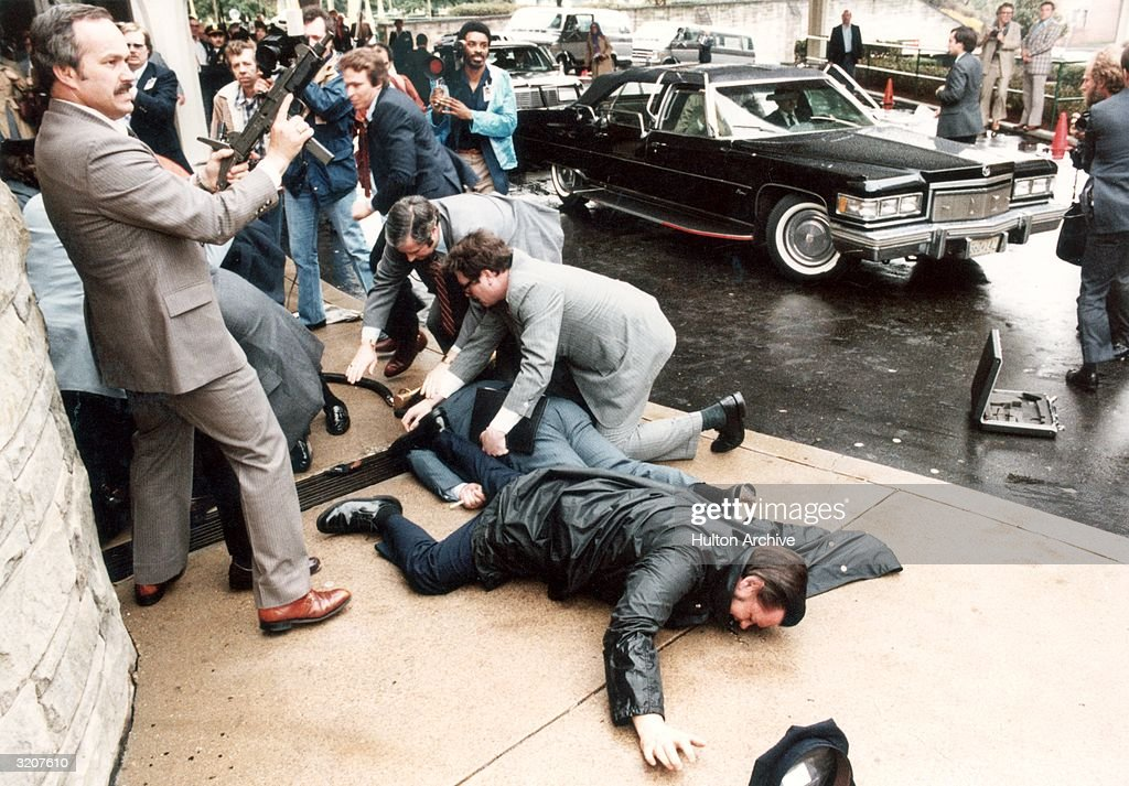 A man holding an automatic rifle men lying on the sidewalk members of the press and cars at the assassination attempt on United States president...