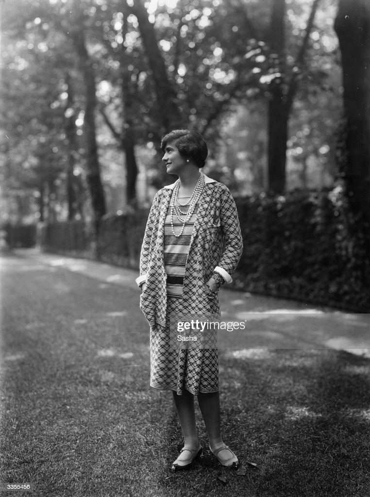 Designer Gabrielle 'Coco' Chanel (1883 - 1971), wearing one of her suits in the grounds at Fauborg, St Honore, Paris.