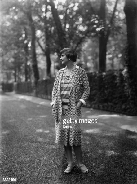Designer Gabrielle 'Coco' Chanel wearing one of her suits in the grounds at Fauborg St Honore Paris