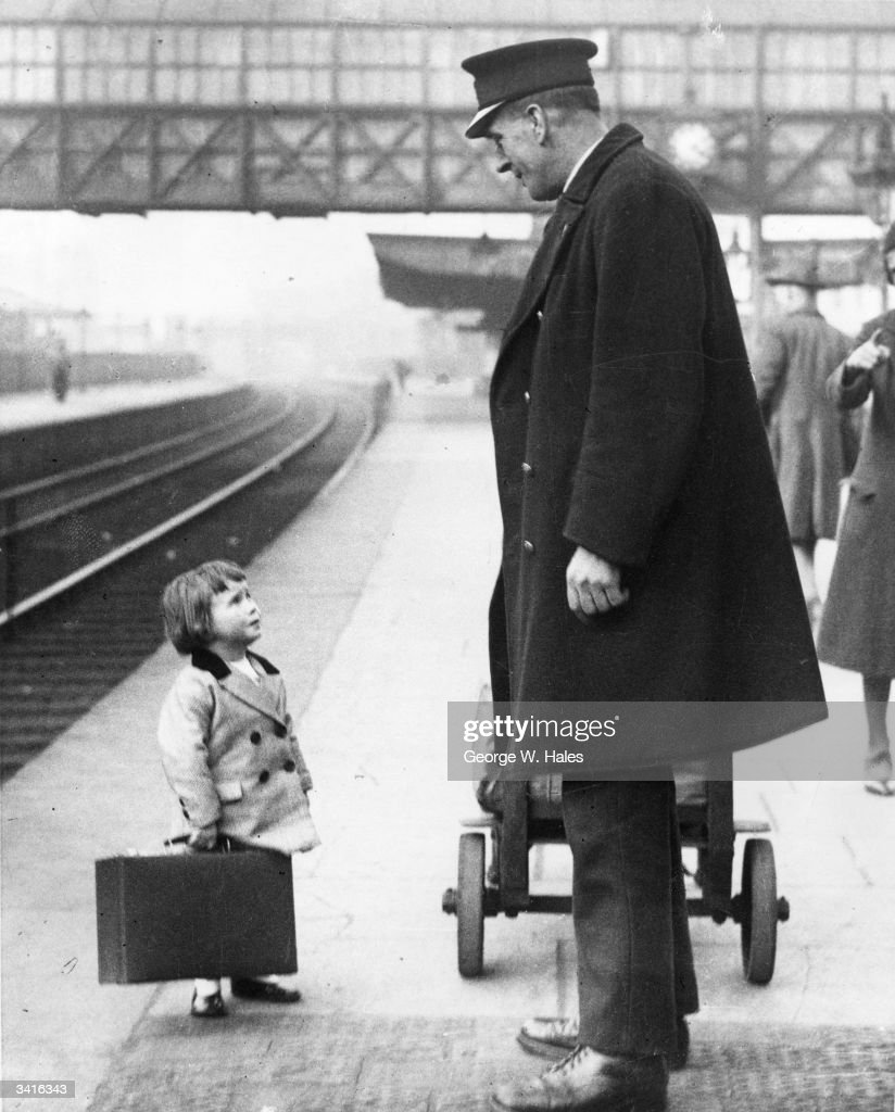 A very young passenger asks a station attendant for directions, on the railway platform at Bristol.
