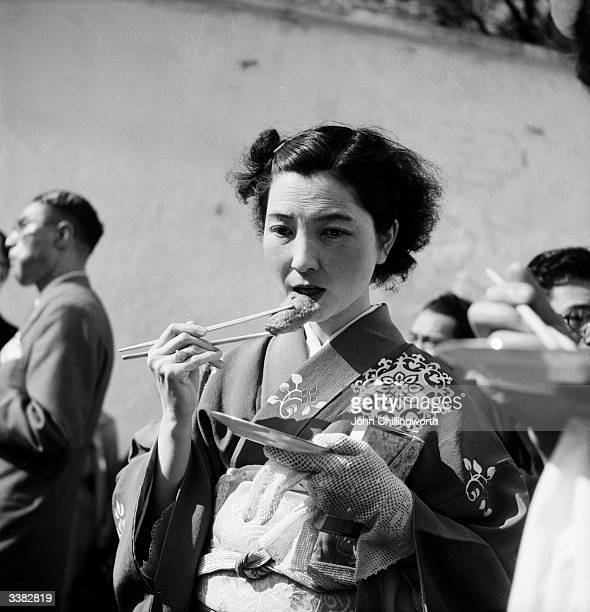 A Japanese girl dressed in traditional kimono and obi eating sushi Original Publication Picture Post 6521 Give This Boy A Break pub 1953