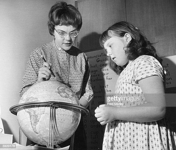 American teacher Miss Tucker at a new school for the children of American servicemen in West Ruislip Middlesex She is showing a pupil Debra Droski...