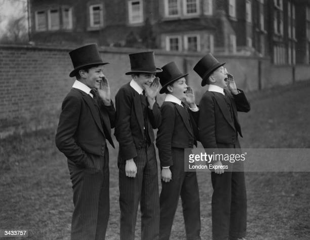 A group of public school boys watch their classmates playing the Eton Wall Game traditionally played between town and school on St Andrew's Day and...
