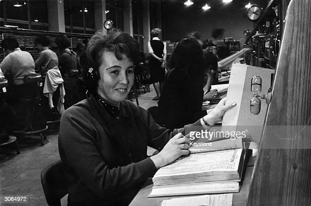 Shirley Boyle answering a query at the Aldershot telephone exchange while an egg timer runs down