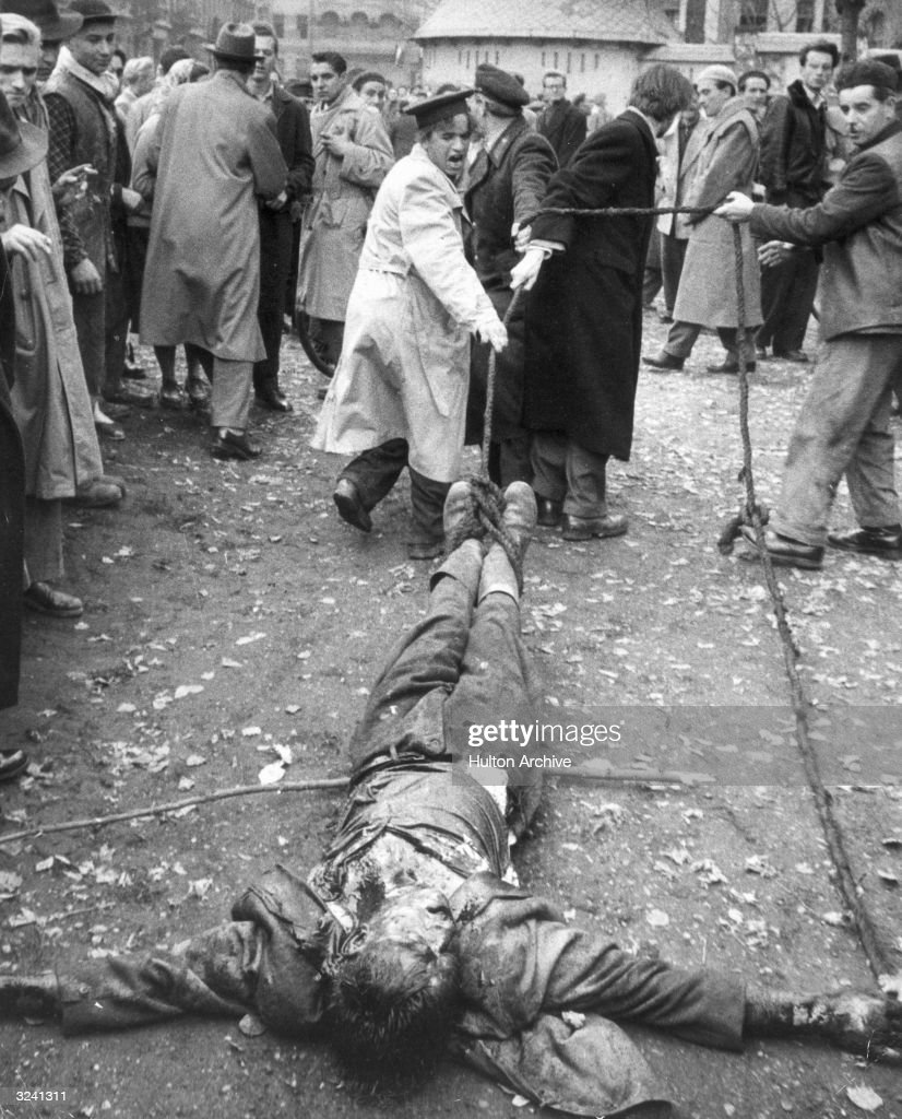 A beaten Hungarian colonel in the AVO, the secret police of the communist regime, is dragged along the ground by ropes attached to his ankles by angry protesters during the popular uprising, Hungary. The attempted revolution was put down by Soviet forces in early November, installing a new Communist puppet government.