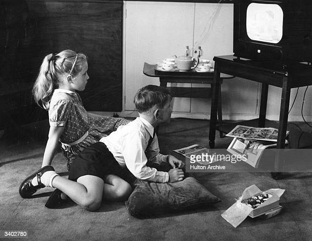 Children eating chocolates in front of the television