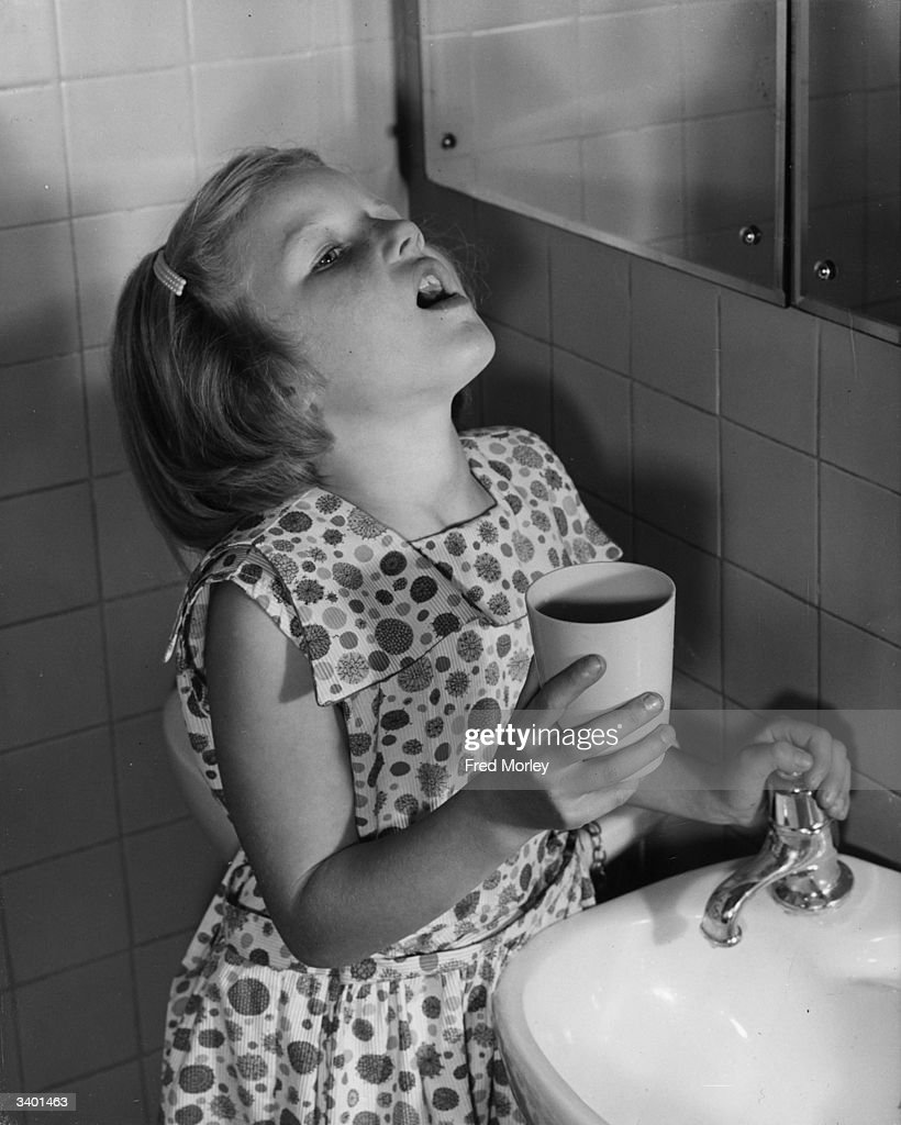 A pupil at the Highbury Quadrant Junior School, Islington, London, having her daily gargle to keep a 'flu virus at bay.