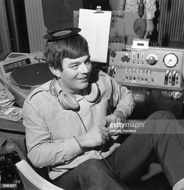 Discjockey Tony Blackburn balancing a single on his head at the opening of BBC Radio's pop music station Radio 1