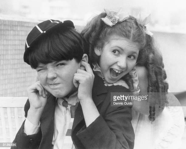 14 year old Adrian Dannatt as 'William' blocks his ears when 12 year old Bonnie Langford as 'Violet Elizabeth Bott' threatens to 'Thream and thream...