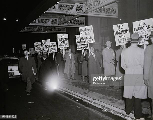 Pickets from various Jewish and Labor organizations carry protesting signs the appearance of the Berlin Philharmonic Orchestra at Carnegie Hall...
