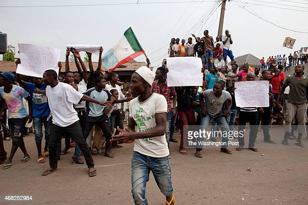 Kaduna Nigeria Nigerians hold signs in celebration as they watch people drag race on the streets of Tundu Wada to celebrate the win of presidential...