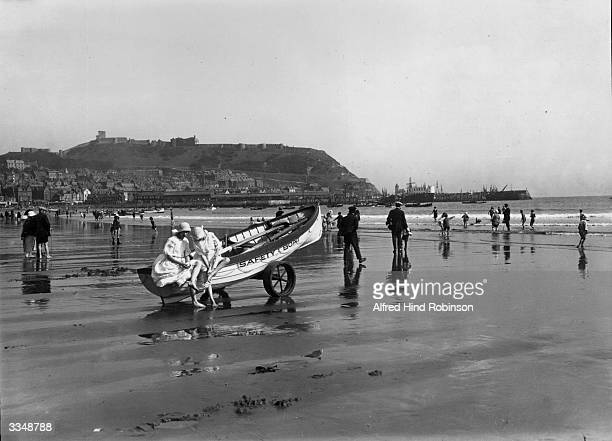 Holidaymakers on the sands at Scarborough Yorkshire The town lies on the hill in the background Two girls sit on a rescue boat drawn up on the sand