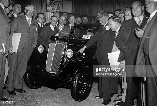 English motor magnate and philanthropist William Richard Morris Nuffield points out features of the new Morris Eight motor car to Morris dealers...