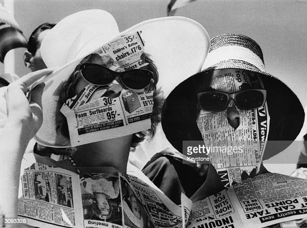 Two girls protect themselves from the fierce glare of the sun with newspapers during the Davis Cup Challenge Tennis Championships in Adelaide