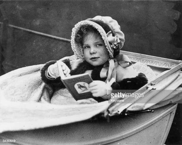 Caroline Blackwood the daughter of the Marchioness of Dufferin and Ava reading a book by Beatrix Potter in her pram