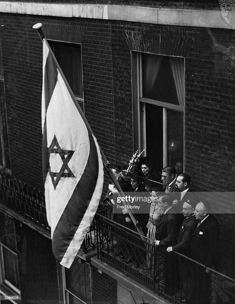 A Jewish flag is unfurled at the Israeli Embassy at Manchester Square, London, following Britain's recognition of the new state of Israel. Embassy staff stand on the balcony.
