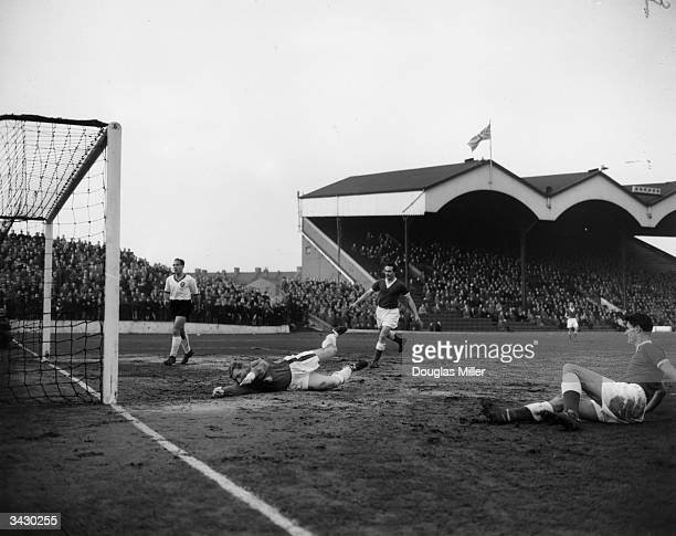 Charlton Athletic player John Hewie scores against Liverpool goalkeeper Young during a match at Charlton's Valley ground
