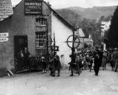 A parade of all ages follow bearers carrying poles decorated with rushes through the streets of Ambleside in the Lake District in the ancient...