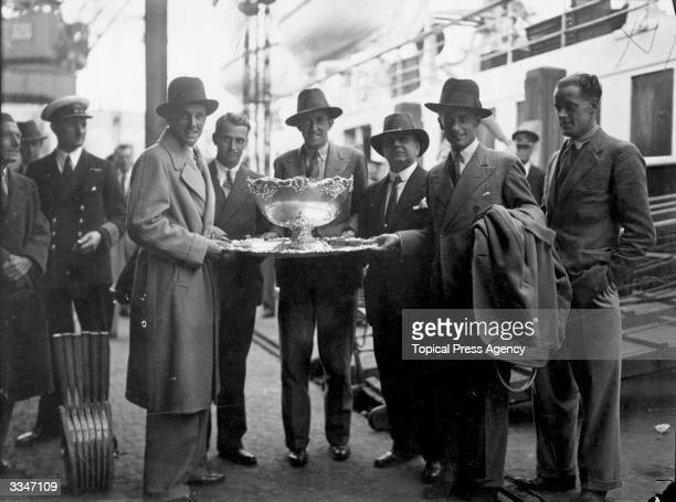 British tennis players Fred Perry Bunny Austin Pat Hughes and H G N Lee holding the Davis Cup with Henry Roper Barrett on arrival at the quayside...