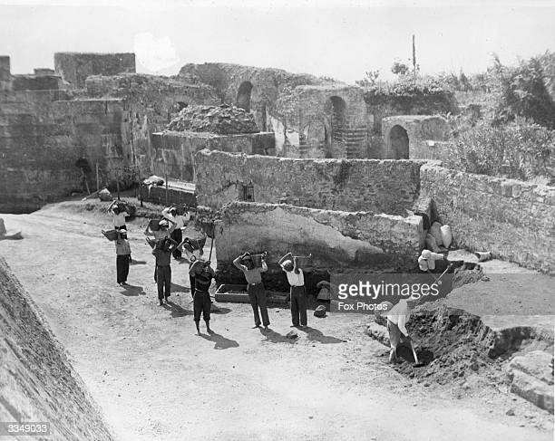 Men excavating walls in the ancient Roman city of Pompeii by hand to reveal the walls which they were built on belonging to another civilisation