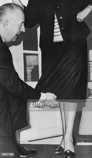 French fashion designer Christian Dior demonstrates his new skirt length for 1953 which he hopes to popularize in the coming season