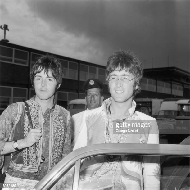 John Lennon and Paul McCartney of the Beatles arrive at London Airport after a trip to Greece