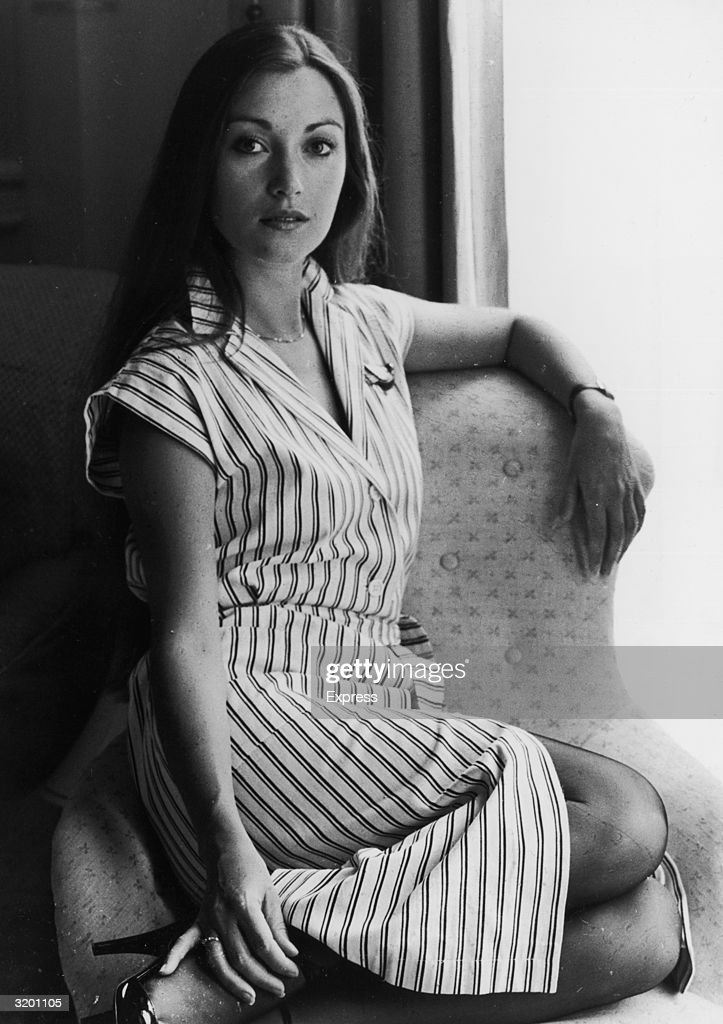 Portrait of British actor Jane Seymour sitting with her legs curled under her and her arm resting on the back of a chair. Seymour is wearing a short sleeve striped dress.