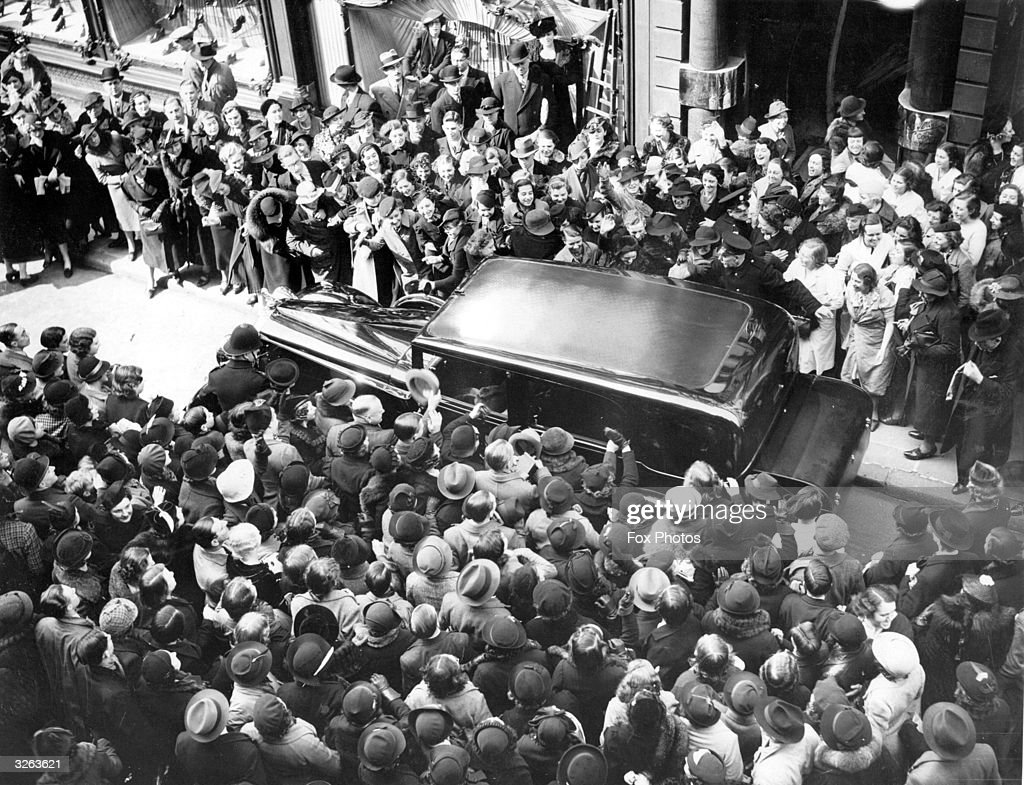 Queen Elizabeth's car is mobbed by shoppers as she leaves New Bond Street after a fitting for her Coronation dress