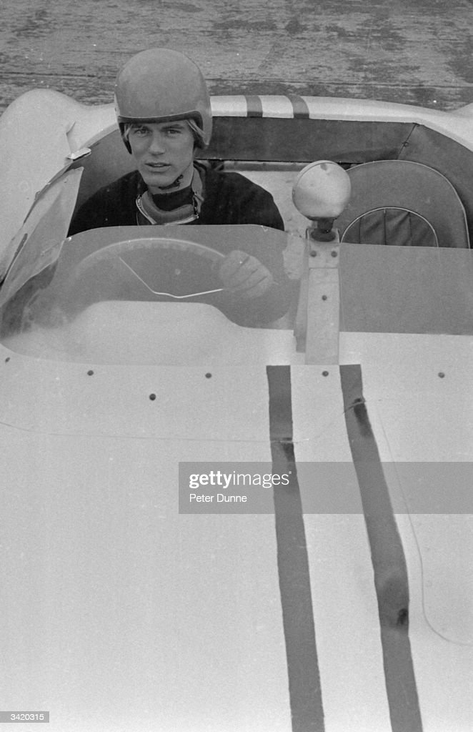 British pop singer and actor Adam Faith (1940 - 2003) sitting in his car during a day of racing at the Silverstone circuit.