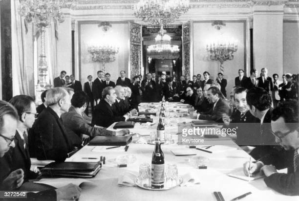 American President Richard Nixon sits opposite Leonid Brezhnev and other Soviet leaders at a conference in Moscow