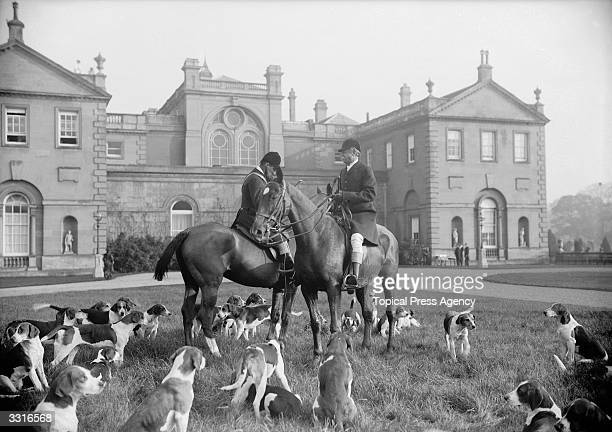Members of the Earl Fitzwilliam Hunt at Clumber surrounded by hounds gather on the grass in front of the Earl's stately home