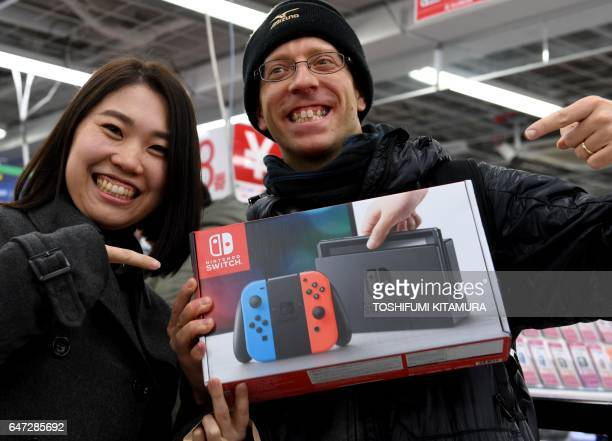 31yearold Nao Imoto and her husband David Flores 34 pose with their newly purchased Nintendo Switch game console at a shop in Tokyo on March 3 2017...