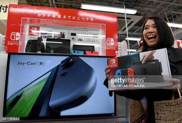31yearold Nao Imoto poses with her newly purchased Nintendo Switch game console at a shop in Tokyo on March 3 2017 Nintendo's new game console Switch...