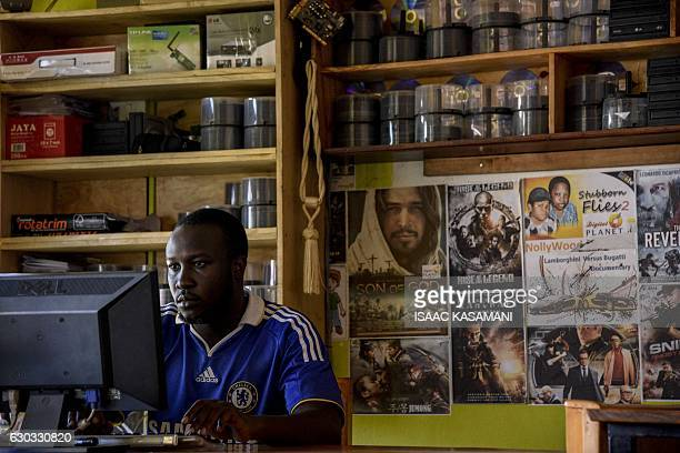 MATSIKO 31yearold video library owner Kenneth Evans Okim works on a computer in his shop in Soroti District about 300 kilometres northeast of the...