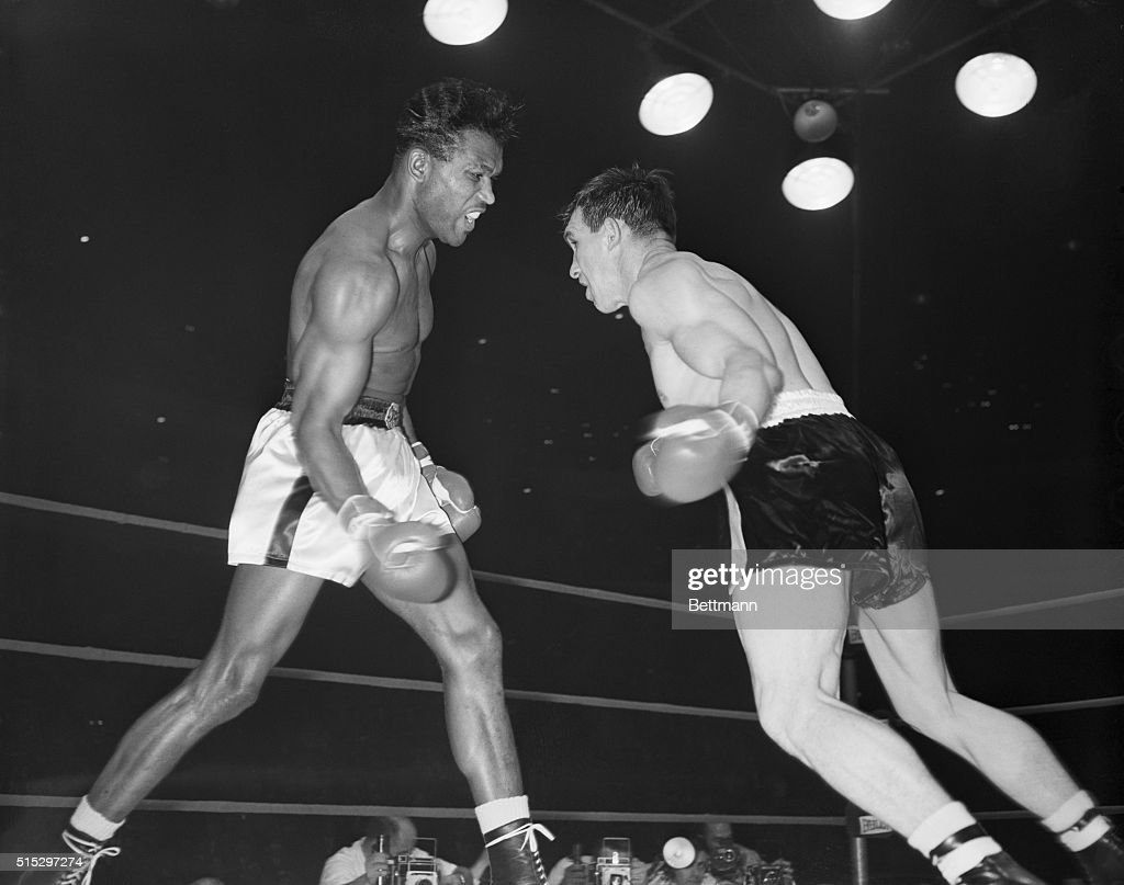 Chicago, IL- Sugar Ray Robinson (R) throws a right to the head of Carmen Basilio during a late round of their middleweight title fight in the Chicago Stadium. Robinson won on a split decision to become the first man in history to win a championship five times.