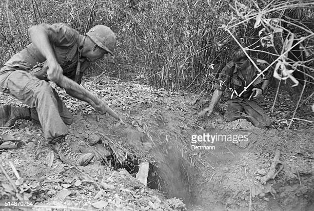 3/25/1967Tay Ninh South Vietnam While a buddy with pistol ready kneels by a GI of the 2nd Battalion 18th Infantry shovels dirt into a tunnel entrance...