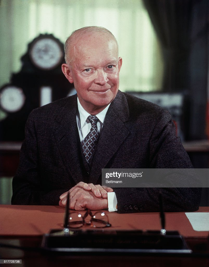 President Eisenhower poses for portrait at his desk in the White House.