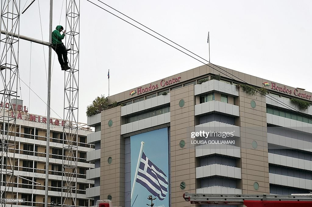 A 35-year-old deaf woman sits on a sculpture installation at Omonia Square, threatening to jump