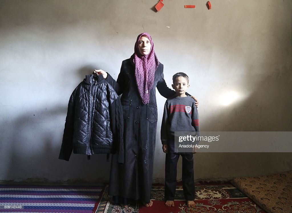 35-years-old Syrian refugee widow mother Emira Hammadi (L), fled from Syria due to ongoing civil-war, poses with her son Mehmet Hammadi (R) as she hold his deceased husband's jacket at a house in Turkey's Syrian border city Hatay's Reyhanli District on February 08, 2016. Emira Hammadi had lost her husband due to a Assad Regime's attacks. Turkey spent US$ 8 Billion and hosts approximately 2 million refugees.
