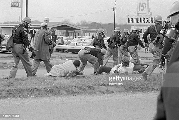 3/7/1965Selma Alabama Wearing helmets and gas masks charging Alabama state troopers pass up fallen Negro demonstrators on the median strip of US...