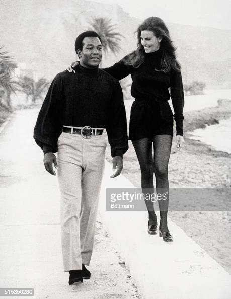 Her raquel walks above him as she and jim brown stroll along a
